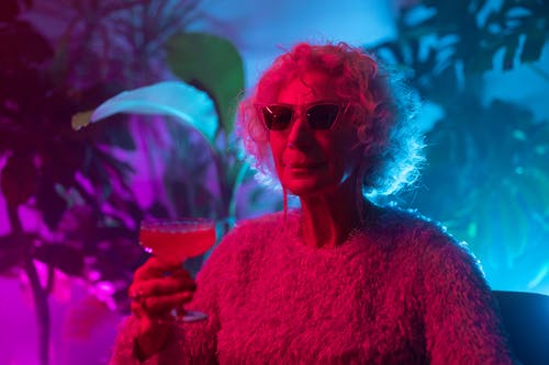 Photo of an Elderly Woman Holding Cocktail