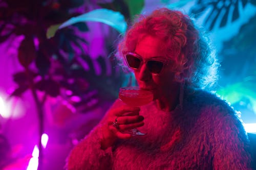 Close-Up Photo of Chic Grandma Drinking Cocktail