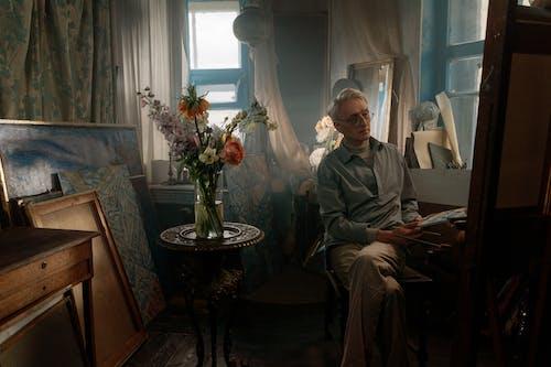 Kostenloses Stock Foto zu älterer erwachsener, blumengesteck, drinnen