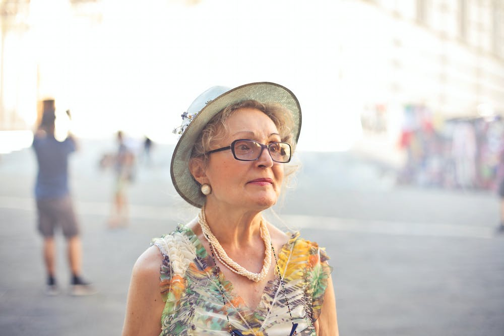 Woman in pastel color sleeveless shirt and white sunhat. | Photo: Pexels