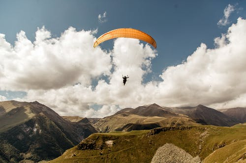 Person in Parachute over Green Mountains