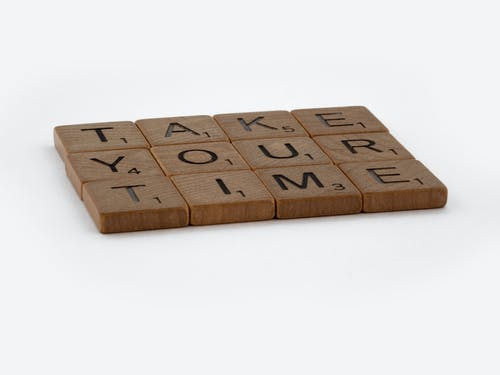 Brown Wooden Scrabble Tiles on White Surface