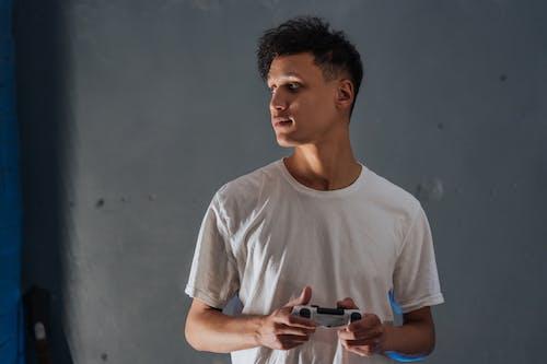 Immagine gratuita di controller di gioco, guardando oltre la spalla, t-shirt girocollo