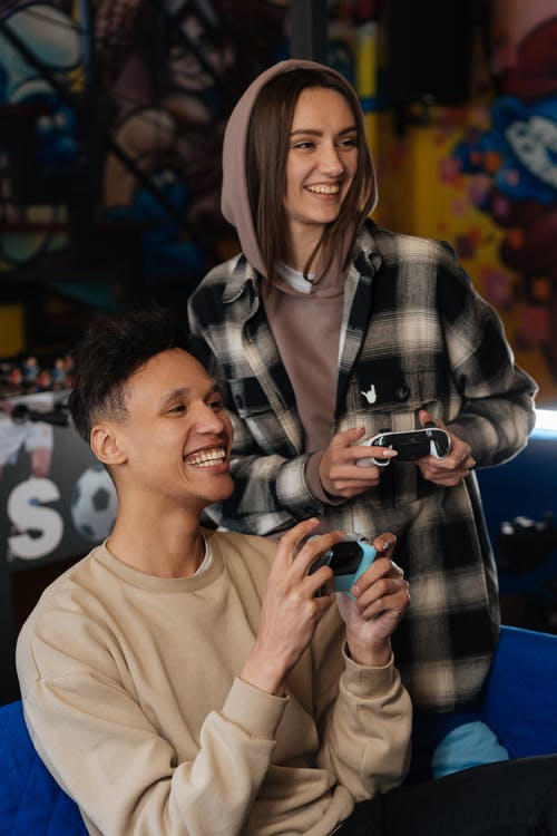 Smiling Man and Woman Holding Game Controllers