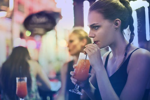 Woman Wearing Black Spaghetti Strap Top and Sipping Drink