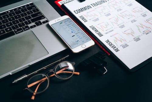 Silver Iphone 6 Beside Black Framed Eyeglasses