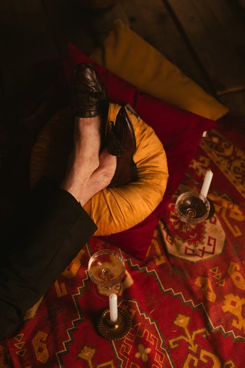 Photo of Person's Legs Resting on a Yellow Cushion