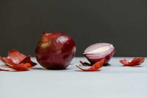 Close-Up Shot of Onions on a White Surface