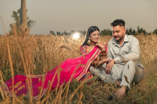 Man and Woman Sitting on Brown Grass Field