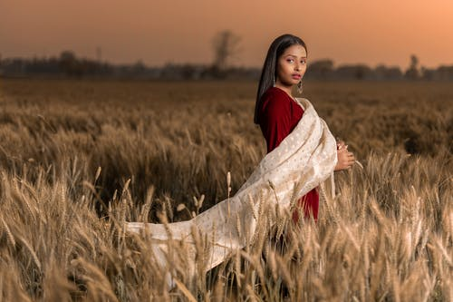 Woman in Brown Scarf Standing on Brown Grass Field