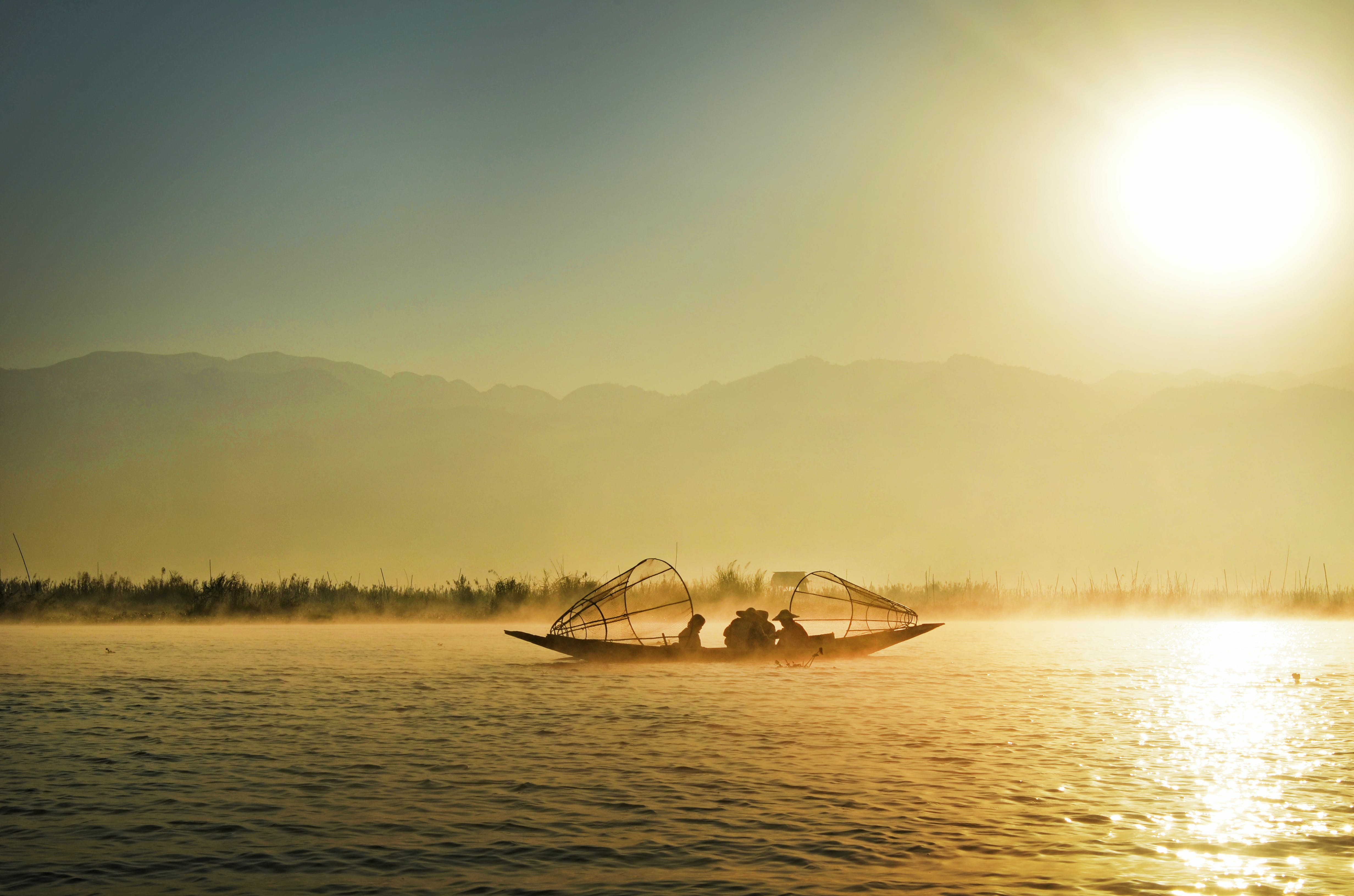 Group of People Riding Boat in the Middle of Water during Sunrise