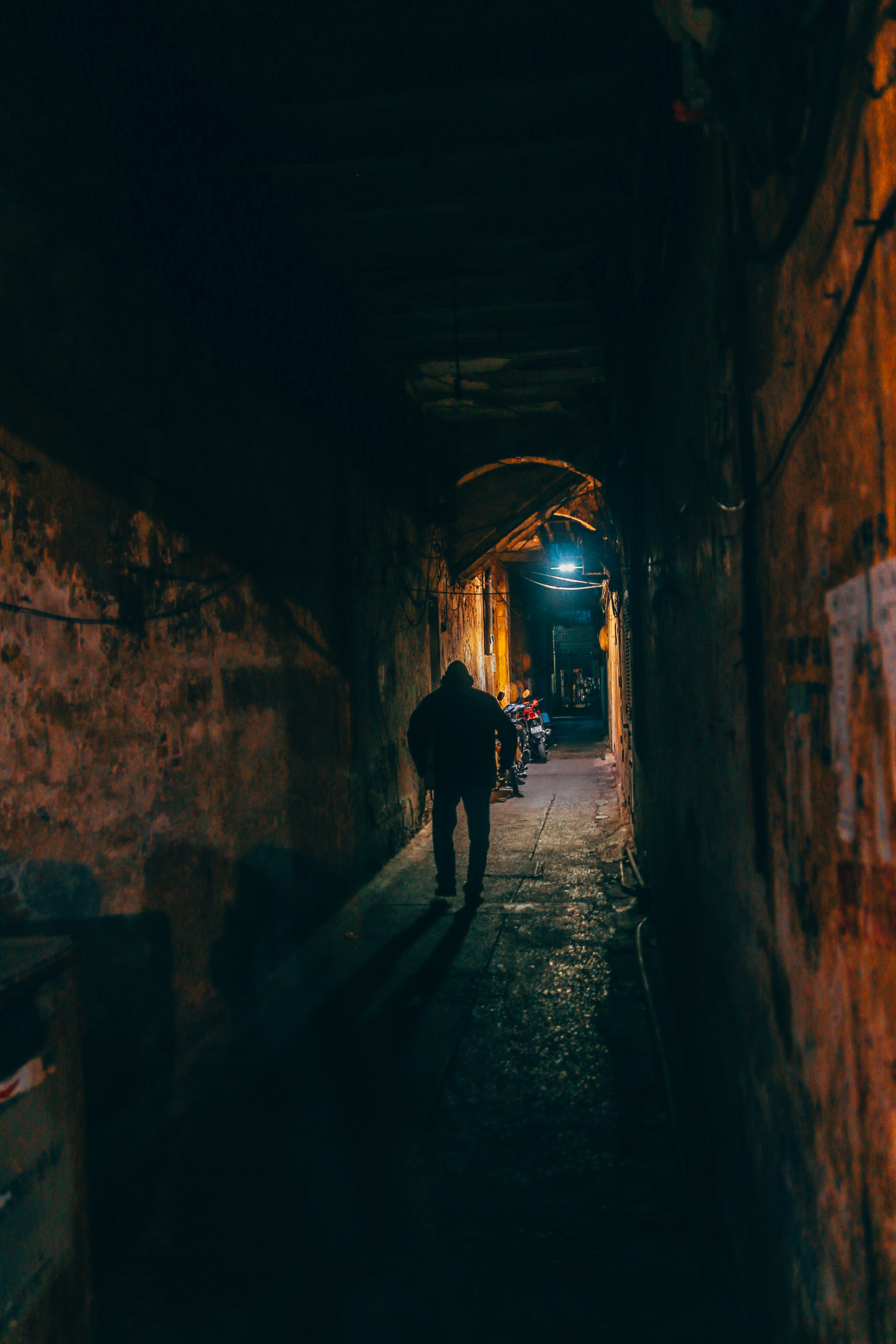 Photo of Person Walking Along Brown Wall Tunnel