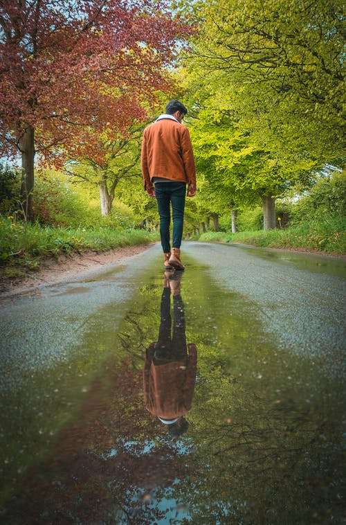 Man in Blue Jacket and Black Pants Walking on Road