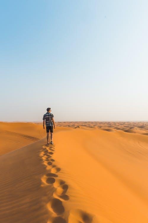 Man in Black Jacket Walking on Desert