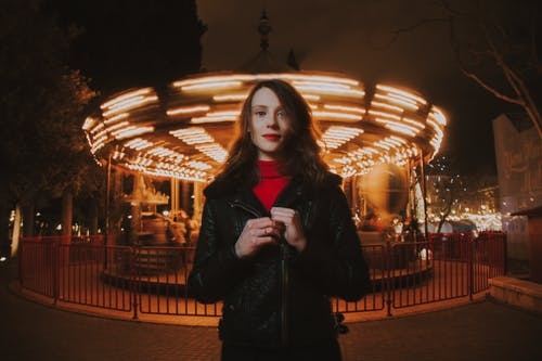 Woman Wearing Black Leather Jacket and Red Turtle-neck Shirt Standing in Front of Carousel Ride