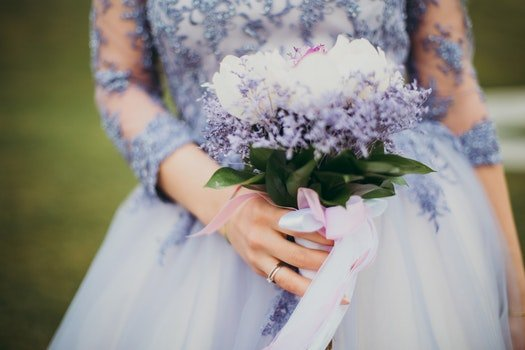 Woman in Blue Gown Holding Bouquet of Flowers