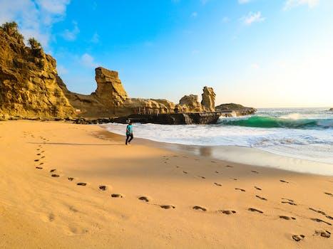 Person Walks on Brown Seashore Near Rock Formations