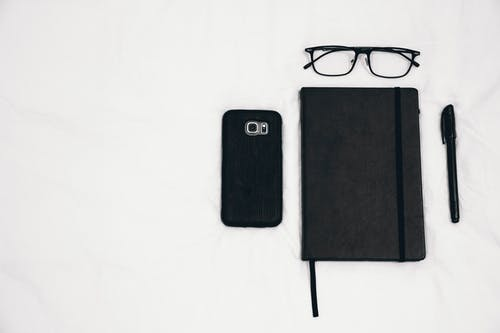 Black Smartphone Beside Planner and Eyeglasses and Pen