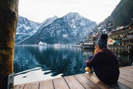 Woman in Purple Sweater Sitting on Wooden Floor With View of Lake and Mountains