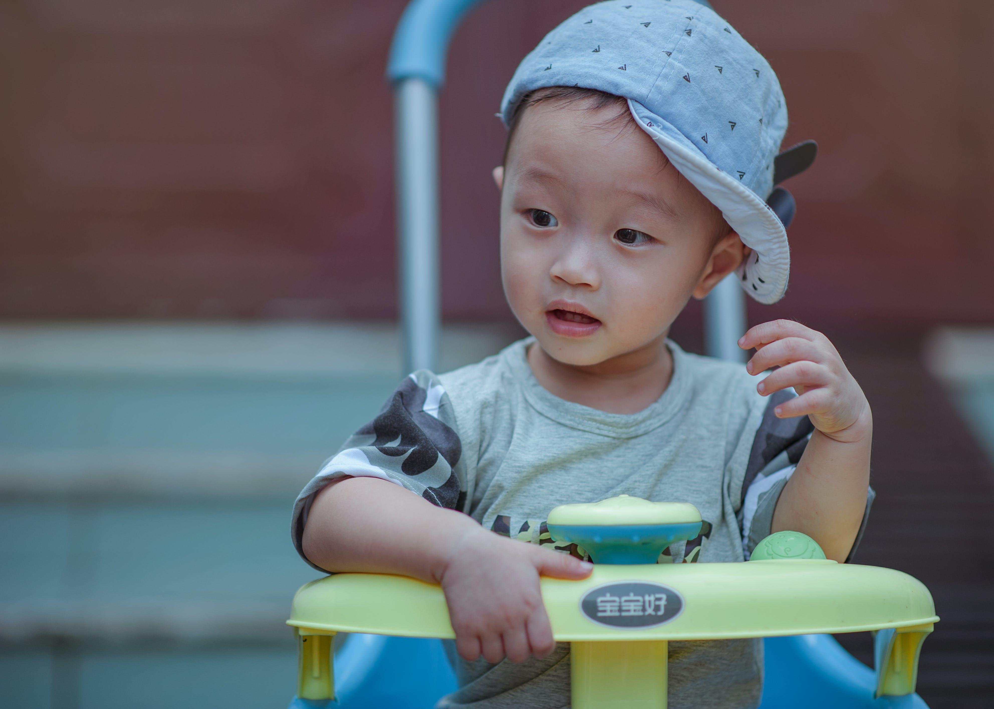 Boy Sitting on Yellow and Blue Trike