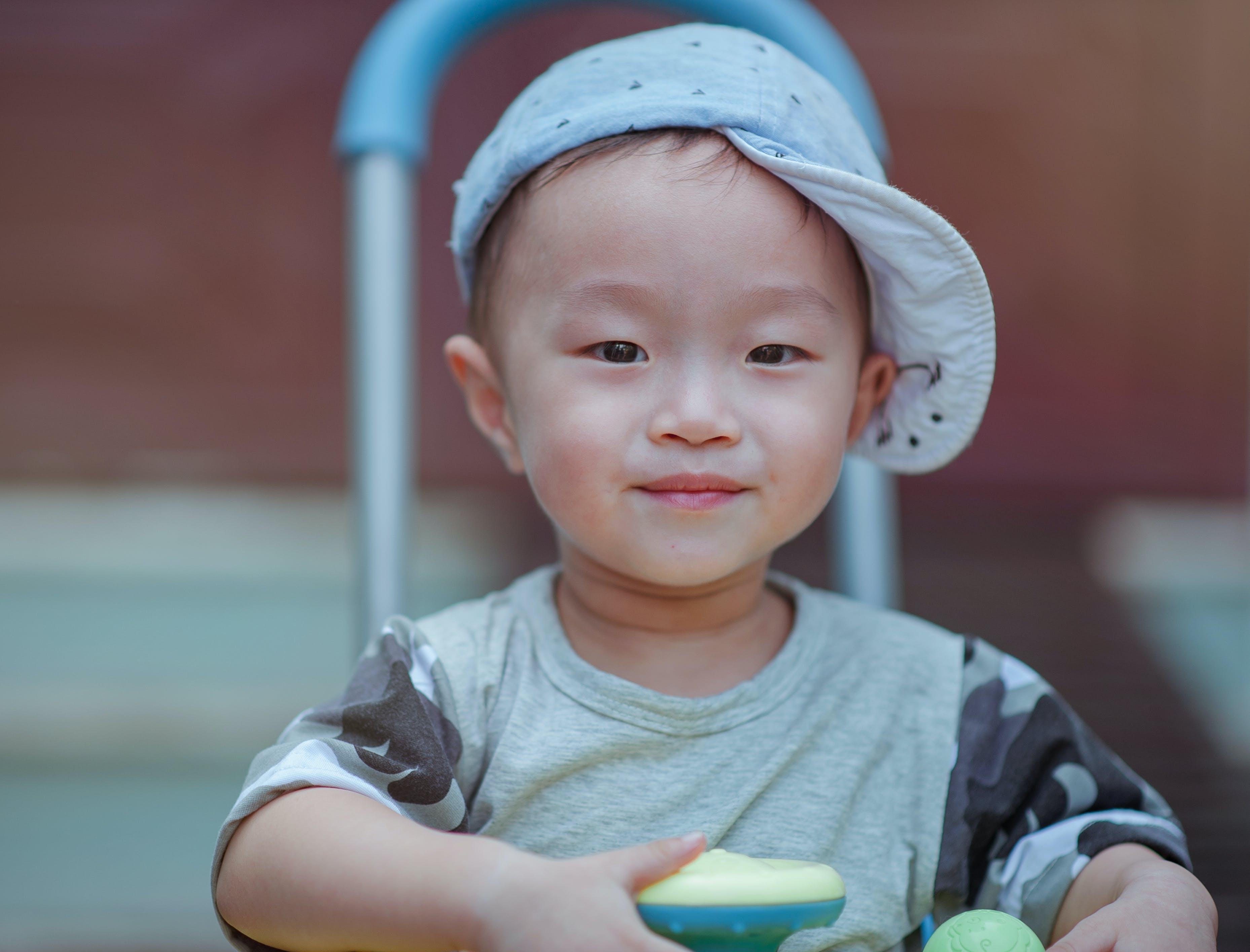 Depth of Field Photo of Boy Wearing Blue Cap