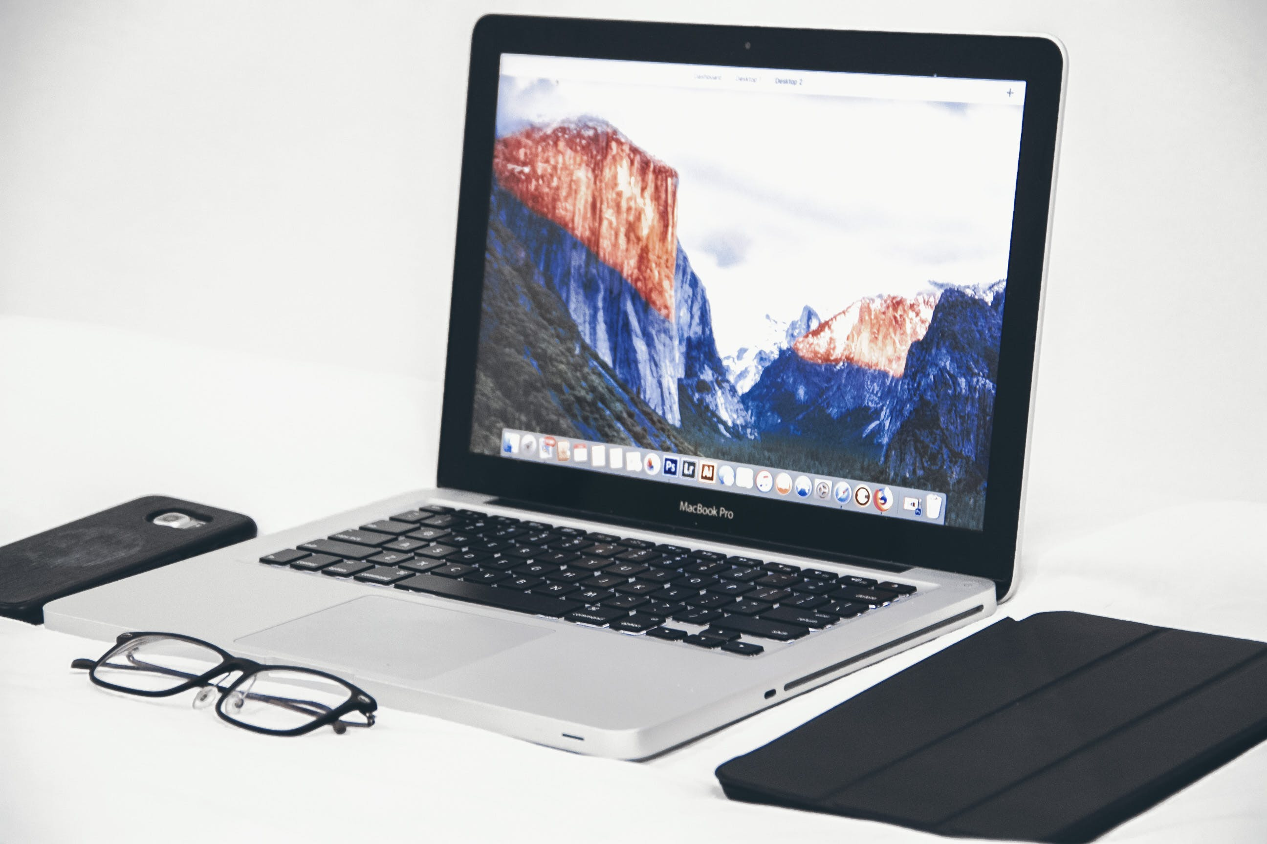 Macbook Air Beside Eyeglasses and Black Smart Case