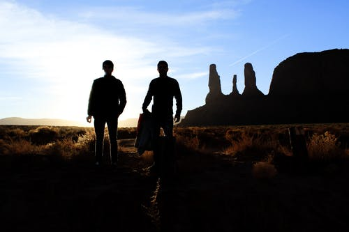 Silhouette of Two Person Standing on the Desert