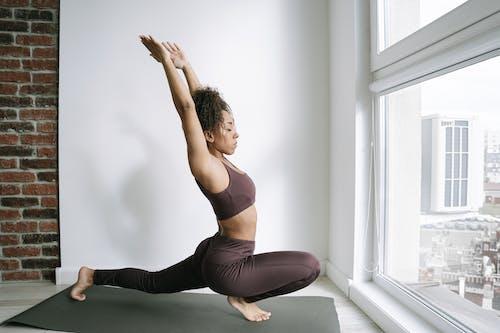 Woman in  Yoga Position Near Floor Window