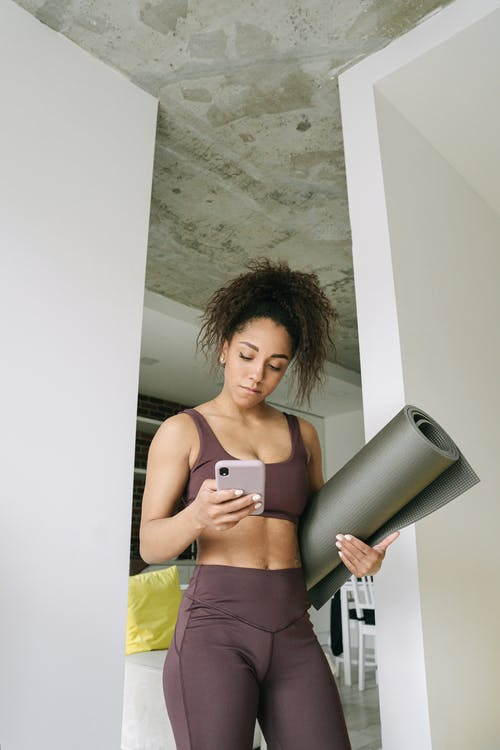 Woman Holding Yoga Mat and Cell Phone