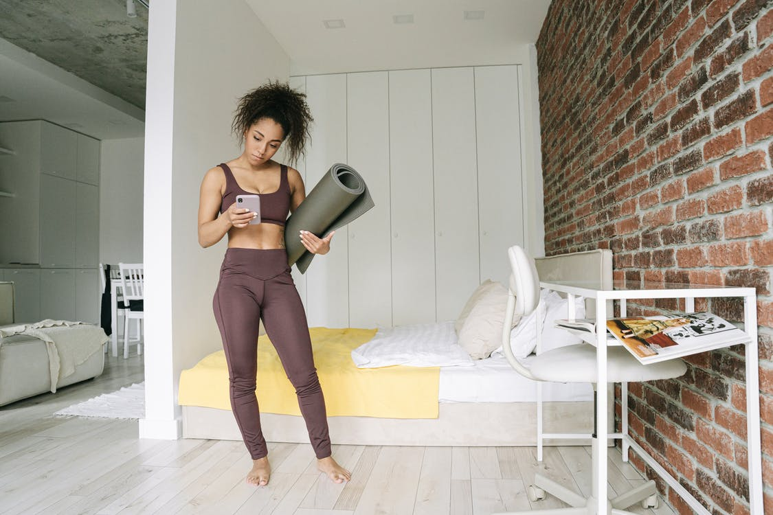 Woman in Bedroom Standing while Using Cell Phone