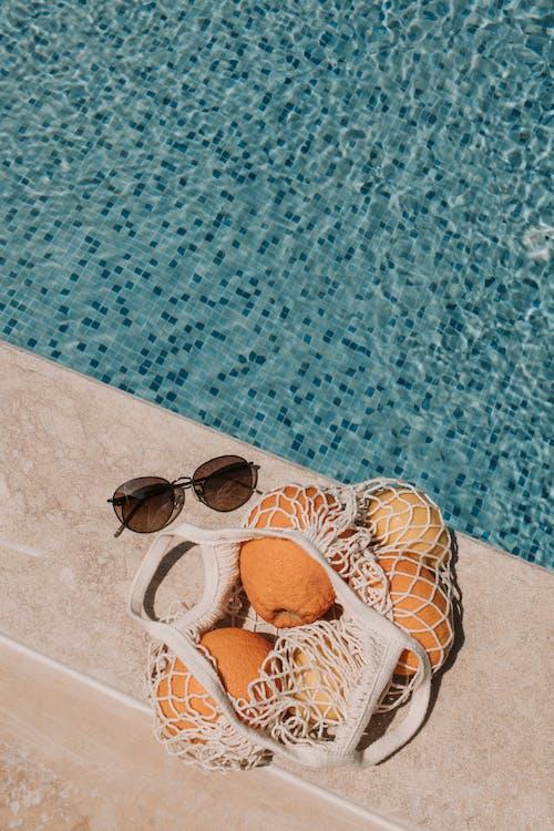 Basket Of Orange Fruits On Poolside