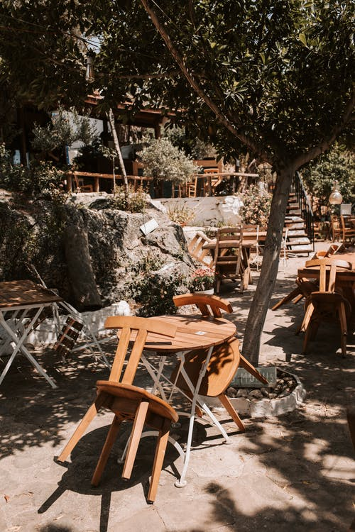 Wooden Chairs And Tables Outside A Restaurant