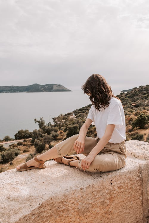 Woman Sitting On Concrete Wall Facing The Sea