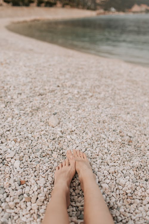 Persons Feet on White and Brown Stones Near Body of Water
