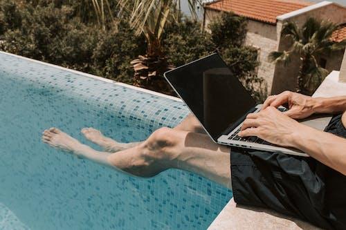 Crop Photo Of Man Using Black Laptop Computer on Swimming Pool