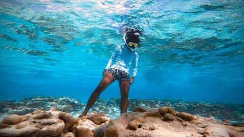 Unrecognizable woman snorkeling underwater