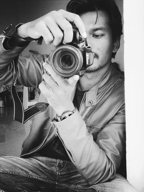 Monochrome Photography of Man Holding Black Nikon Camera