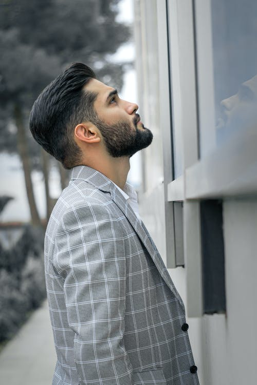 Man in White and Black Checkered Dress Shirt Looking at the Window