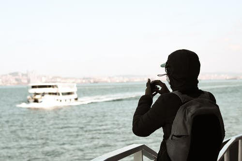 Back view of unrecognizable man with backpack in jacket admiring ship in wavy sea using small camera
