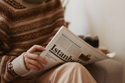 Crop unrecognizable female in ornamental sweater reading newspaper article while sitting in armchair in house room