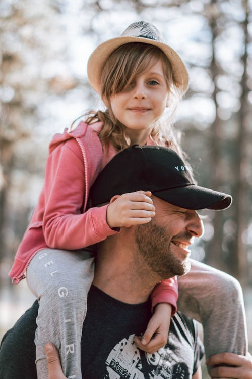 Delighted father in cap giving ride on shoulders to cute daughter while spending weekend together in park