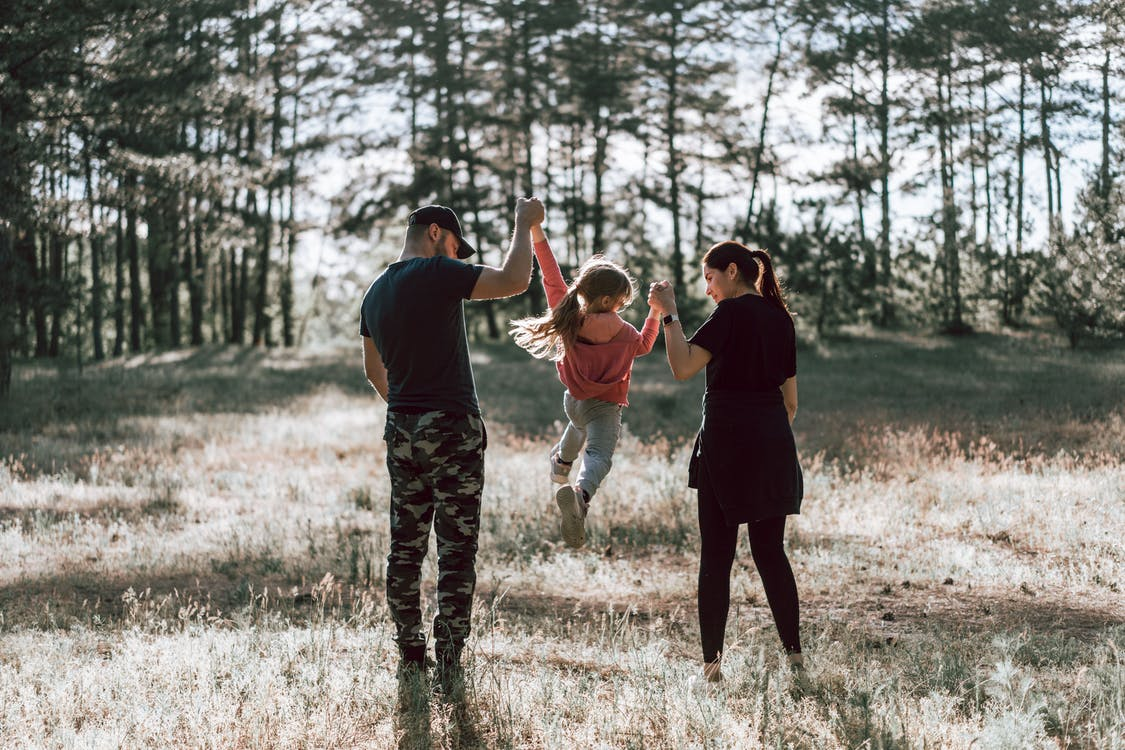 Happy family walking in forest