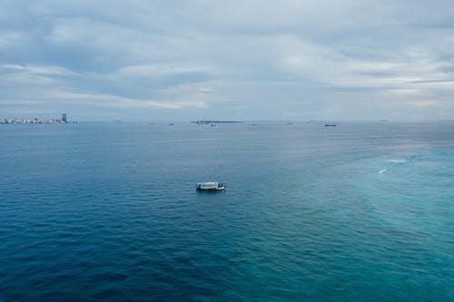 White Boat on Sea Under White Sky
