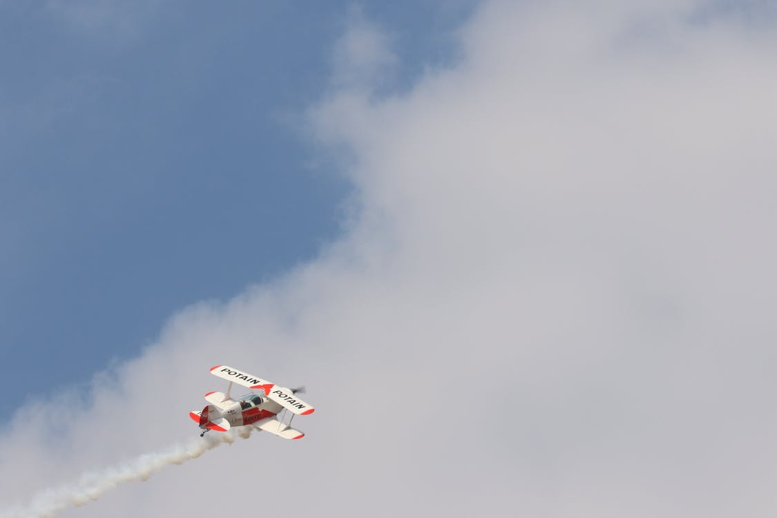 White and Red Biplane Flying during White Cloudy Day