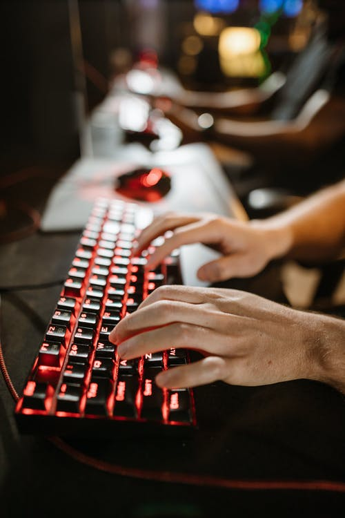 Close-Up Photo of Person's Hands on Mechanical Keyboard