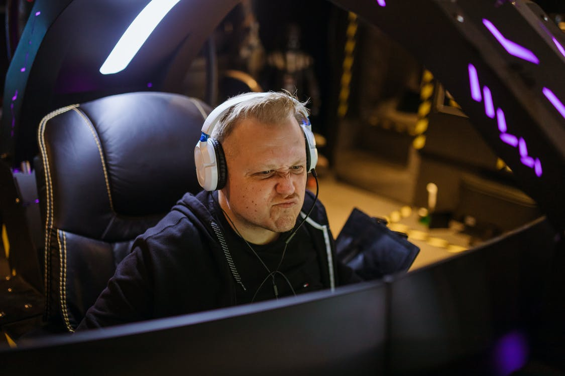 A Man Wearing White Headphones Playing a Computer Game