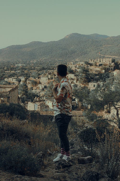 Full body side view of anonymous male traveler standing on grassy hill while contemplating aged buildings located in rural area