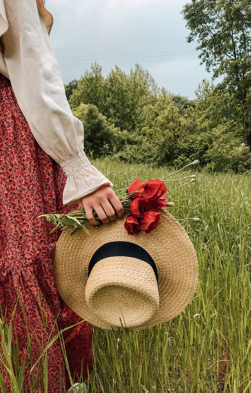 Woman with hat and flowers in field