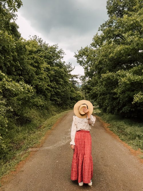 Full body of unrecognizable female in stylish outfit covering face with hat while standing on walkway in forest on cloudy day
