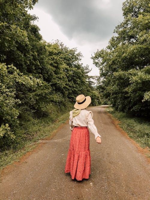 Woman in hat walking along rural road